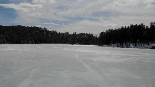 a drone low flies over frozen center lake in custer state park south dakota - custer state park stock videos & royalty-free footage