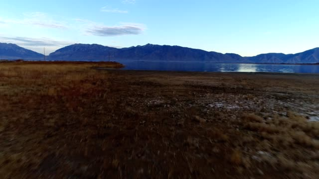 a drone low flies over lincoln beach and utah lake in provo utah - provo stock-videos und b-roll-filmmaterial