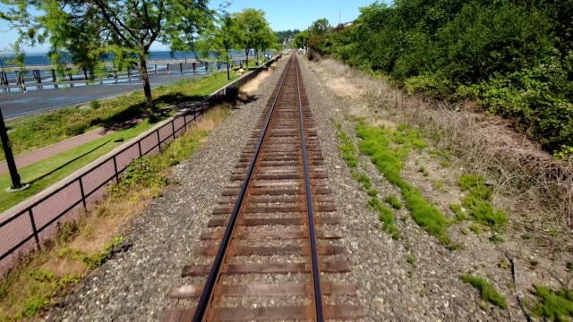 a drone low flies over railroad tracks by water in white rock canada - tramway stock-videos und b-roll-filmmaterial