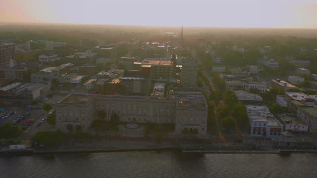 vídeos de stock, filmes e b-roll de drone medium to wide aerial alton lennon federal building and riverwalk on cape fear river waterfront in downtown wilmington at sunrise - wilmington carolina do norte