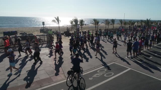 drone moves out with runners after start on boardwalk adjacent to beach and atlantic ocean women only - querfeldeinrennen stock-videos und b-roll-filmmaterial