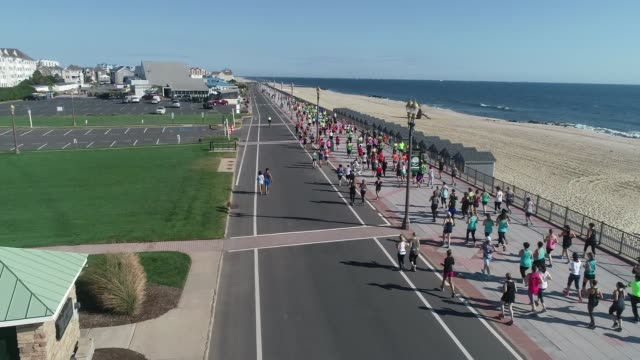 drone moves out with runners after start on boardwalk adjacent to beach and atlantic ocean - salmini stock videos and b-roll footage