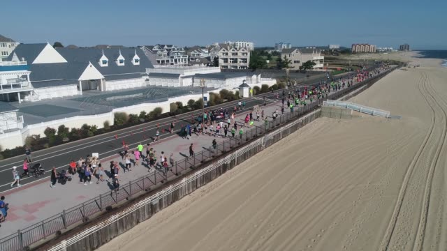 drone moves over beach to runners after start on boardwalk - joggerin stock-videos und b-roll-filmmaterial