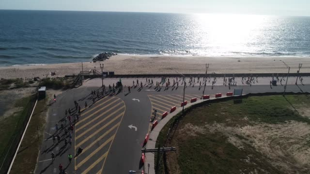 drone moves past runners to atlantic ocean and sunrise - salmini stock videos and b-roll footage