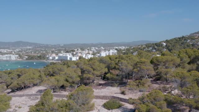 vídeos y material grabado en eventos de stock de drone moving over trees on mountain by tourist resort against sky during sunny day - ibiza, spain - bahía