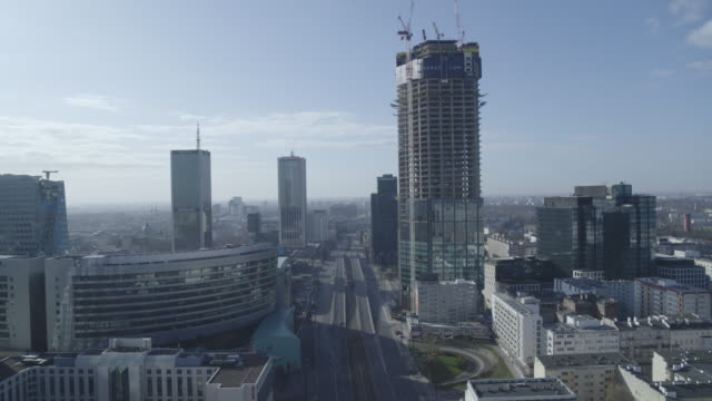 drone of a deserted downtown boulevard through skyscrapers on boulevard alej jana pawla ii in daytime warsaw during the corona shutdown 2020 - aprile video stock e b–roll