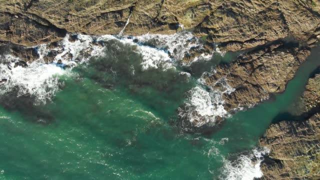 drone offers a birds eye view of a choppy ocean as waves crash into jagged rocks and rugged cliffs in south devon, uk. - extreme terrain stock videos & royalty-free footage