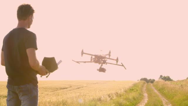 stockvideo's en b-roll-footage met pan drone marktexploitant die van een drone af te nemen - piloot