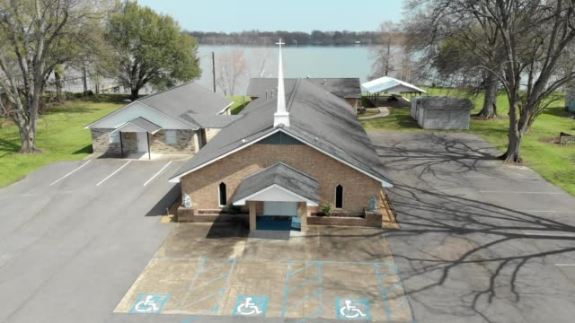 a drone orbits a church on a lakeside in ferriday louisiana - südliche bundesstaaten der usa stock-videos und b-roll-filmmaterial