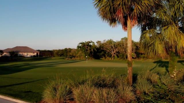 a drone orbits a dark green golf course hole in bradenton florida - trefferversuch stock-videos und b-roll-filmmaterial