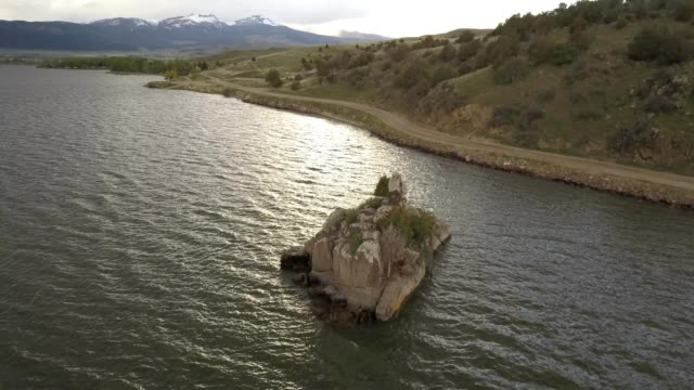 vídeos de stock, filmes e b-roll de a drone orbits a rock island on a lake in bozeman montana - bozeman