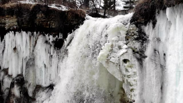 A drone orbits an icy waterfall in Minneapolis Minnesota
