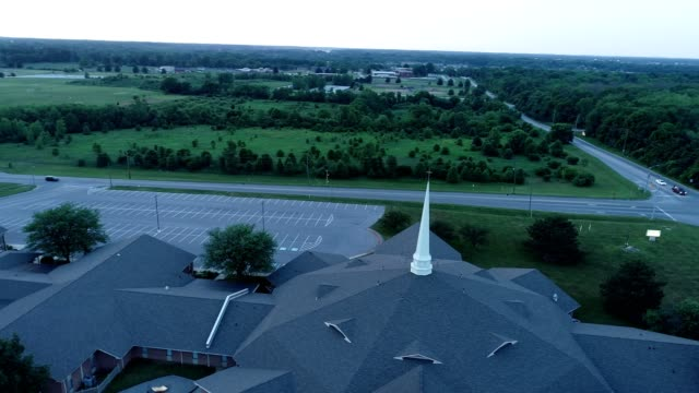 a drone orbits around a first baptist church steeple in indianapolis indiana - kirchturmspitze stock-videos und b-roll-filmmaterial