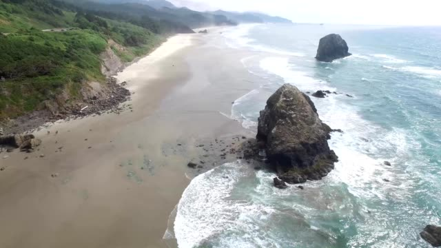 a drone orbits haystack rock in cannon beach oregon - cannon beach stock videos & royalty-free footage