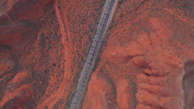 drohne über eine alte, lückenhafte straße in der nähe von canyonlands, utah - moab utah stock-videos und b-roll-filmmaterial