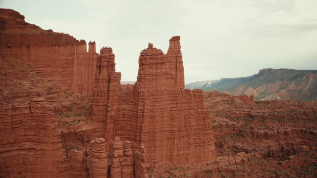 drone over desert and canyons near moab: fisher towers - natural arch stock videos & royalty-free footage