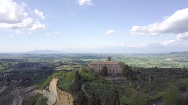 vidéos et rushes de drone over hills, woods and an ancient farmhouse near volterra, tuscany, italy - toscane