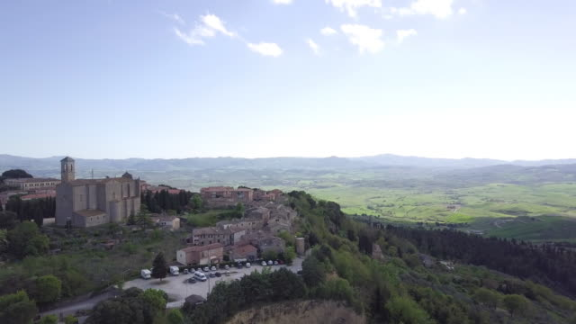vidéos et rushes de drone over hills, woods and an ancient village near volterra, tuscany, italy - toscane