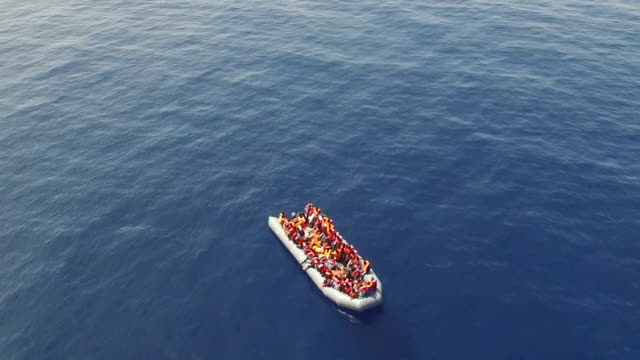 drone overhead of an empty migrant boat full of lifejackets after rescue - flüchtling stock-videos und b-roll-filmmaterial