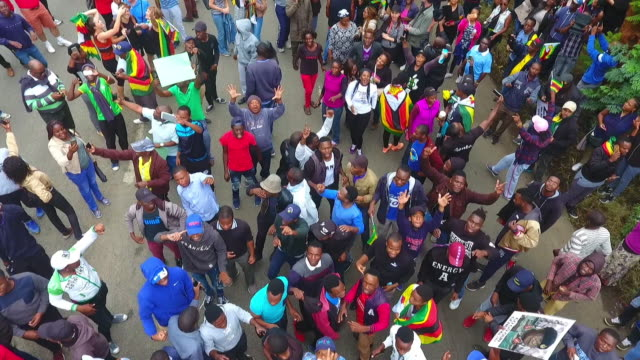 Drone pan down and pan up shot of crowds on Samora Machel Ave Harare during street celebrations following Robert Mugabe's resignation as president of...