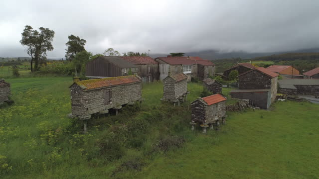 drone panning over traditional barns on plants with houses in village against cloudy sky - galicia, spain - galicia stock videos & royalty-free footage