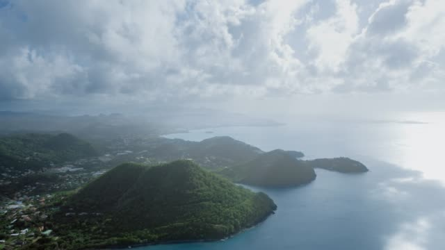 vidéos et rushes de drone panorama of the blue sea and coast with mountains, dense forest and the city, clouds float from above (saint lucia) - arbre tropical