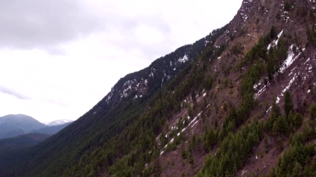 A drone pans down a mountain to a lake in Thompson Falls Montana