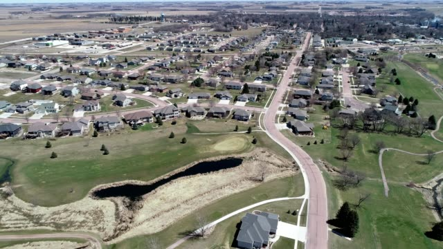 a drone pans over a golf course next to a residential neighborhood in dell rapids south dakota - south dakota stock-videos und b-roll-filmmaterial