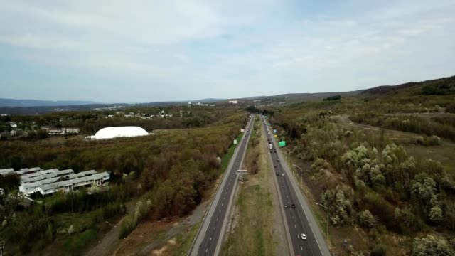 a drone pans over a highway towards va hospital in wilkes-barre township pennsylvania - wilkes barre stock videos & royalty-free footage