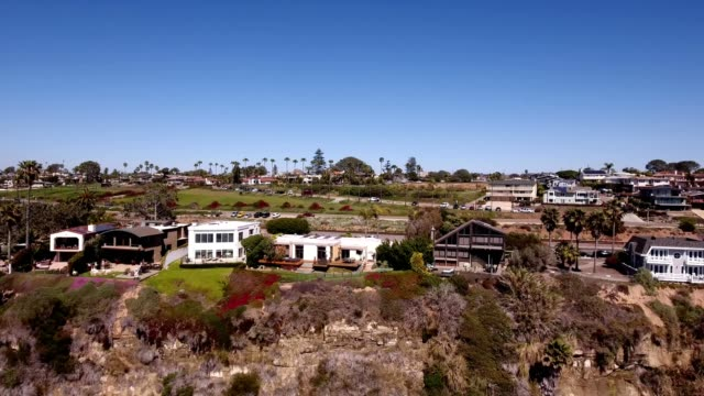 a drone pans over coastal homes in encinitas california - dronebase stock videos and b-roll footage