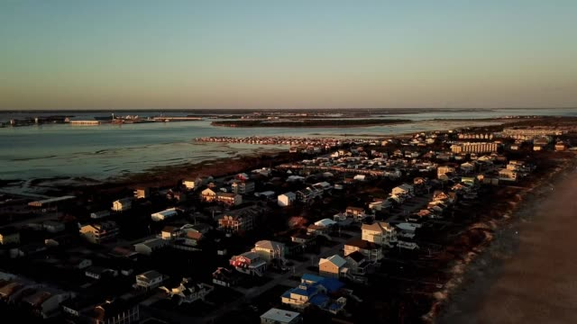 a drone pans over sunset lit oceanfront homes in atlantic beach north carolina - atlantic beach north carolina stock videos & royalty-free footage
