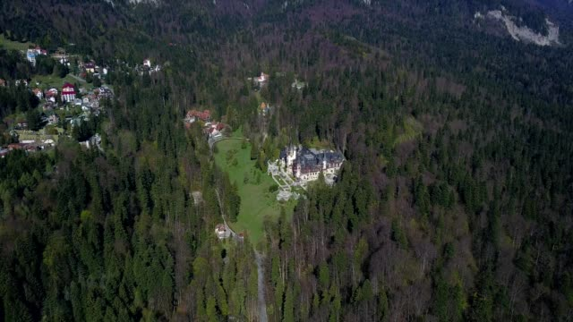 A drone pans up from the Peles Castle towards its neighboring mountains in Sinaia Prahova Romania