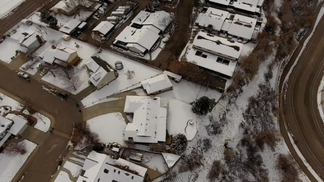 a drone pans up over a snow covered neighborhood towards the mountains in provo utah - provo stock-videos und b-roll-filmmaterial