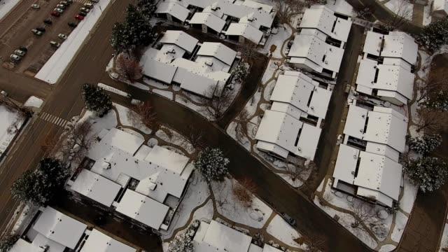 vídeos de stock, filmes e b-roll de a drone pans up over a snow covered neighborhood towards the mountains in provo utah - provo