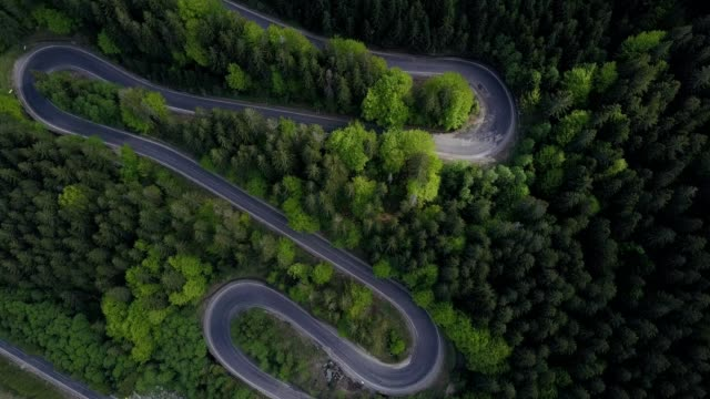 a drone pans up over a winding road near cheia prahova county romania - hair accessory stock videos & royalty-free footage