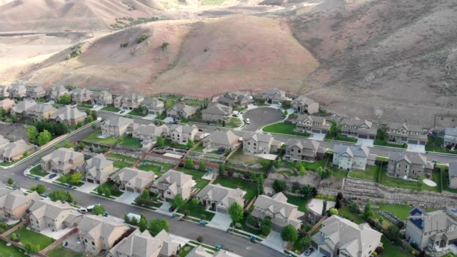 a drone pans up over suburban ho uses to view the mountains beyond in lehi utah - lehi stock videos & royalty-free footage