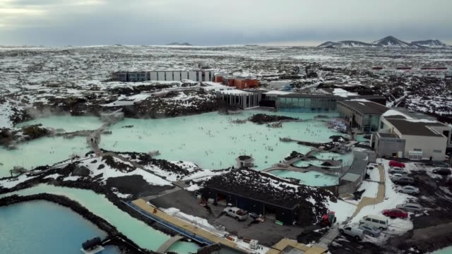 A drone partially orbits a Blue Lagoon in Grindavík Iceland