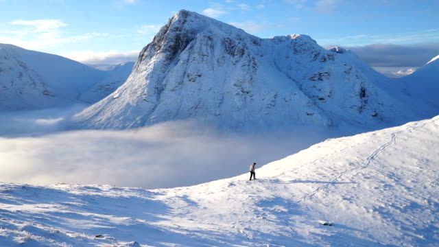 険しい雪の高原の山を飛ぶドローンの視点 - 冠雪点の映像素材/bロール