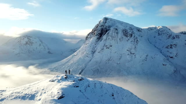 drone perspective flying over rugged snowy highland mountains - scottish highlands stock videos & royalty-free footage