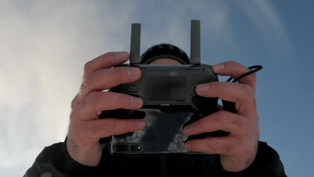 a drone pilot using his remote control to fly his drone, high technology device usage, close up of man's hands working - drone pilot stock videos and b-roll footage