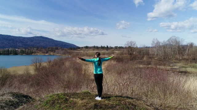 drone point of view adult woman with arms outstretched standing on lakeshore - sun salutation stock videos & royalty-free footage