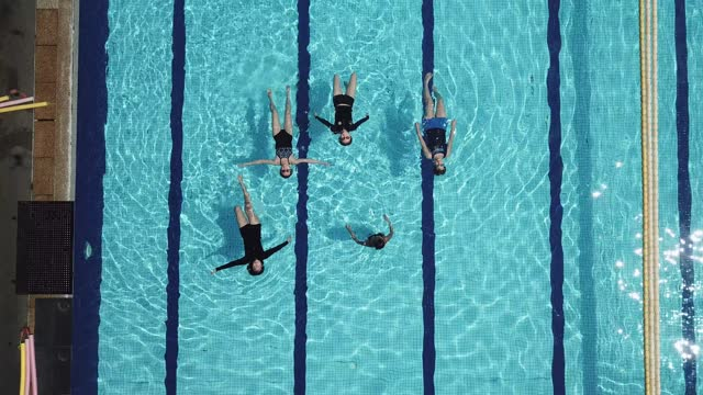 drone point of view directly above swimming pool coach instructor teaching her student swimming skill - hobbies stock videos & royalty-free footage