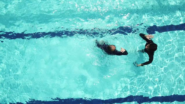 drone point of view directly above swimming pool coach instructor teaching his senior student swimming skill - instructor stock videos & royalty-free footage