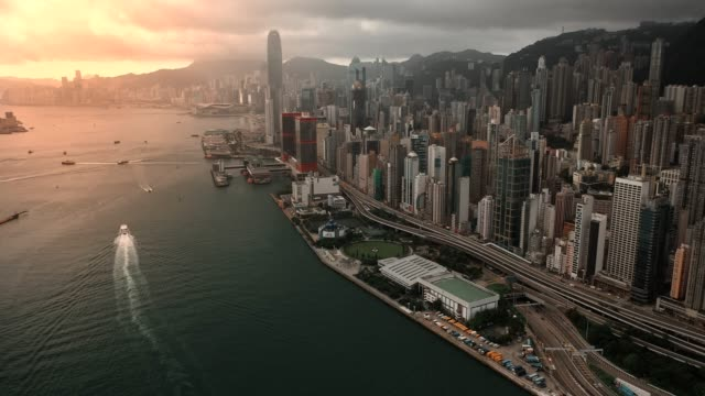 drone point of view : ferry boat headed to victoria harbour at dusk - central district hong kong stock videos & royalty-free footage
