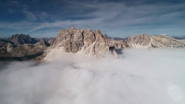 drone point of view flying towards a mountain ridge above the clouds, dolomites, italy - tre cimo di lavaredo stock videos & royalty-free footage