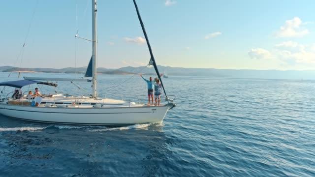 4k drohne sicht freunde auf segelboot am ruhigen, sonnigen blauen ozean, real-time - segelmannschaft stock-videos und b-roll-filmmaterial