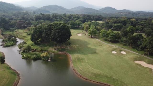 stockvideo's en b-roll-footage met de meningsgolfer van de drone die golf in golfcursus in melaka speelt - breed
