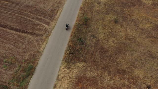 drone point of view man riding motorcycle on road - motorcycle stock videos & royalty-free footage