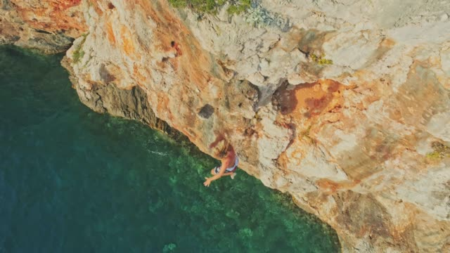 4K Drone point of view man rock climbing, falling into sunny ocean, real time