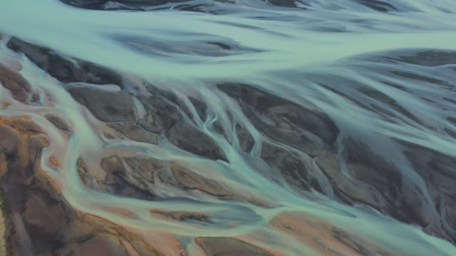 drone point of view of a braided river then tilting up to reveal surrounding landscape, iceland - natürliches muster stock-videos und b-roll-filmmaterial